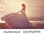 bride walking along sea coast | Shutterstock . vector #1023916954