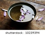 old metal bowl with water and flower petals - stock photo