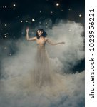 Small photo of attractive goddess stands in the clouds in a luxurious, gold, sparkling dress. Whimsical hairstyle. Against the backdrop of a star and space. Art Photography. Cute princess in fog, mist, haze smoke