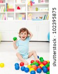 Happy toddler playing with colorful plastic balls - stock photo