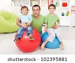 Fun with gymnastic balls - young boys playing with their father - stock photo