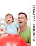 Toddler and his father playing with gymnastic ball - closeup - stock photo