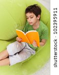 Boy practice reading relaxing on inflatable armchair - stock photo