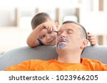 little boy painting his father... | Shutterstock . vector #1023966205