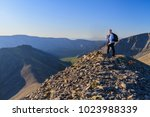 Small photo of A young woman with a backpack and alpenstock stands on top of the mountain against the backdrop of distant beautiful mountains and ridges.