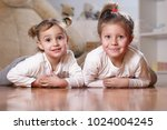 portrait of two sisters lying... | Shutterstock . vector #1024004245