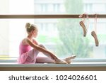 ballerina in pink dress sitting ... | Shutterstock . vector #1024026601