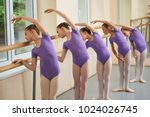 Small photo of Group of ballerinas training at ballet barre. Young ballet girs in purple leotards practicing at ballet class. Tips for beginning ballet.