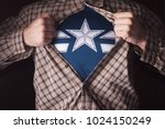 Small photo of Superhero Tears off his Shirt on a dark Background. Tearing the plaid shirt on his chest. The star on his chest.
