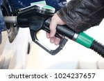 hand holds a nozzle to refuel a ... | Shutterstock . vector #1024237657