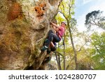 young girl climbs a rock with... | Shutterstock . vector #1024280707