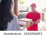 smiling delivery man in red... | Shutterstock . vector #1024296091
