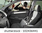A thief wearing a robbery mask trying to steal a purse bag in a automobile - stock photo