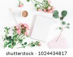 Stock photo office desk with notebook rose flowers eucalyptus branch pink paper blank flat lay top view 1024434817
