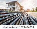 steel rebar for reinforcement concrete at construction site with house under construction background - stock photo