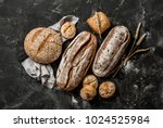 Bakery - gold rustic crusty loaves of bread and buns on black chalkboard background. Still life captured from above (top view, flat lay).