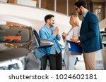 young couple choosing new car... | Shutterstock . vector #1024602181