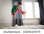 little boy jumping on bed in... | Shutterstock . vector #1024614475