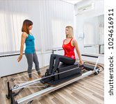 Small photo of Woman exercising on Pilates reformer with personal trainer.
