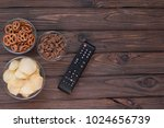 Small photo of Chips, croutons, snacks. TV remote on the background of a wooden table. leisure. Leisure.