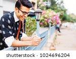 handsome indian man using... | Shutterstock . vector #1024696204