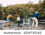 little boy is skimming pebbles... | Shutterstock . vector #1024735165