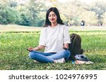 woman practicing yoga on green... | Shutterstock . vector #1024976995