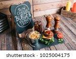 cheeseburger on a pretzel bun... | Shutterstock . vector #1025004175