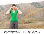 Small photo of The girl tourist standing and doing acupressure on the ears with open eyes against the mountainous steppes, behind the sun is shining