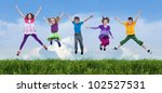 Happy children jumping on the spring field - stock photo