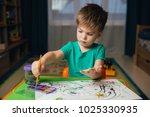 little boy draws a brush and... | Shutterstock . vector #1025330935