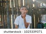 old man smoking cigarette or... | Shutterstock . vector #1025339371