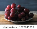 bunch of red grapes on plate on ...   Shutterstock . vector #1025349595