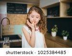 little girl licking fingers... | Shutterstock . vector #1025384485