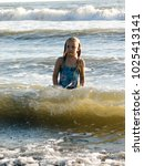 little girl playing in the waves | Shutterstock . vector #1025413141