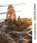 little girl with sand castle | Shutterstock . vector #1025413441