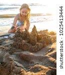 little girl with sand castle | Shutterstock . vector #1025413444