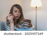 depressed woman eats cake.  sad ... | Shutterstock . vector #1025457169