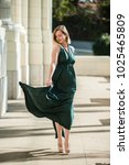 Small photo of Beautiful blond walking with confidence and glee as her emerald green halter top dress dancing with each step.