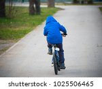 little boy riding a bicycle a... | Shutterstock . vector #1025506465