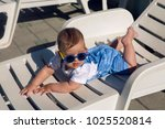 Small photo of child in a denim suit and sunglasses lying on a plastic chaise longue