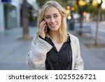 young woman walking talking on... | Shutterstock . vector #1025526721