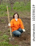 Female gardener plants tree  in spring garden - stock photo