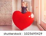 little blonde girl holding a... | Shutterstock . vector #1025695429