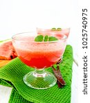 Small photo of Jelly airy watermelon with mint in two glass bowls, a spoon on a green towel against a light wooden board