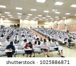 Small photo of Blur environment in Thai entrance examination room that arrange students to seat in line and row. Their emotion are intend and strain.