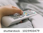 female hand holds the tv remote ... | Shutterstock . vector #1025903479
