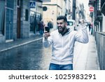 Stock photo lucky young man with fist up celebrates victory holding cellphone on rainy street in the city full 1025983291