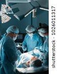 multiethnic surgeons operating... | Shutterstock . vector #1026011317