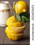 Fresh yellow sliced lemon with sugar on a wooden board. - stock photo